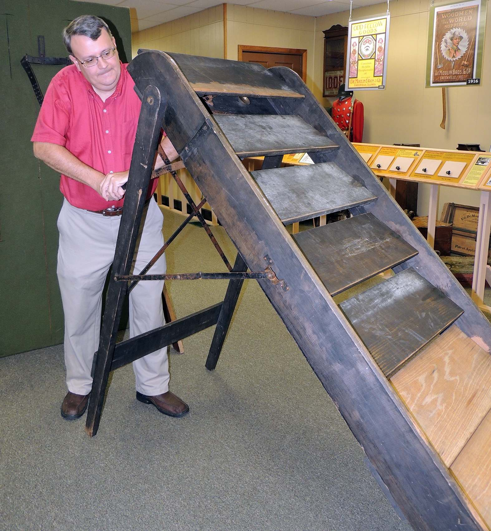 DeMoulin Museum curator demonstrates the trick to the sliding stairs.
